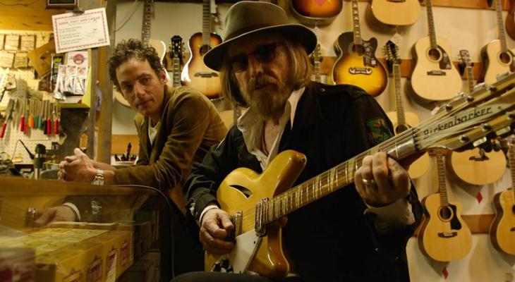 Jakob Dylan watching a musician in a guitar shop