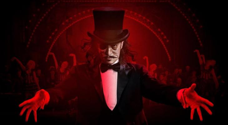Person in a top hat and bow tie against a red background