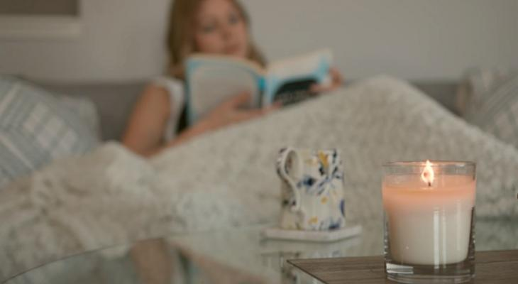 Woman reading a book with a candle on a table