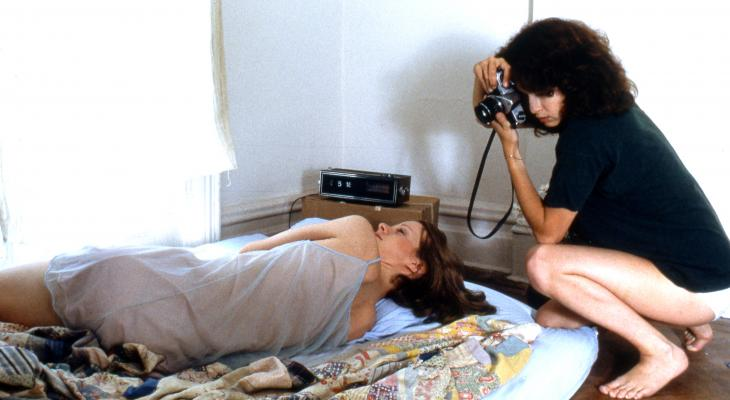 woman lies in bed while another woman photographs her