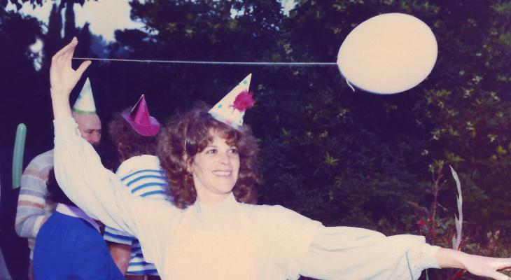 Gilda Rader wearing a party hat and holding a balloon