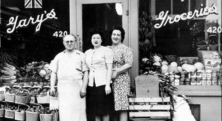 Three people stand in front of an old shop