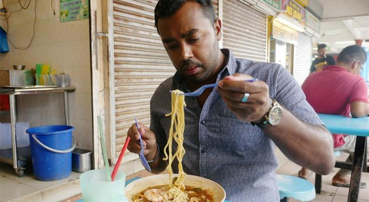 Suresh Doss eating a bowl of noodles at a restaurant