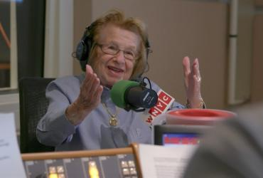 Dr. Ruth speaking into a microphone