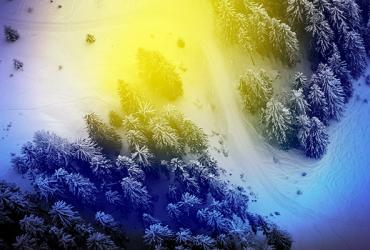 An aerial view of a field and evergreens covered with snow with a blue and yellow aura filter.