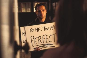 "Man holding sign that says ""To Me, You Are Perfect."""