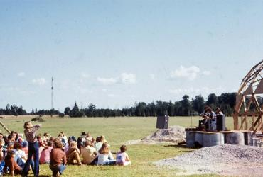 People sitting on a field listening to live music