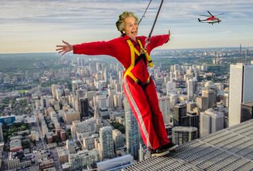 Photoshopped image of an elderly woman leaning out over the edge of the CN tower in a red bodysuit.