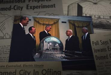 People talking in front of a domed city model