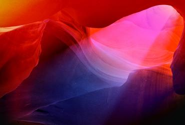 A colourful aura photograph with splashes of blue, pink, orange and black, of Antelope Canyon with a beam of light shining down.