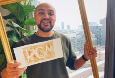 Portrait of host Kiron holding a sign that reads ROM