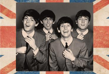 Black and white photo of the beatles, with border of the British flag