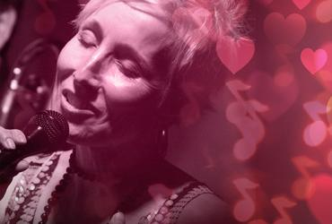 Jazz vocalist Tanya Willis singing with a pink background covered in hearts and music notes