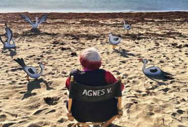 Agnès Varda sitting on a beach