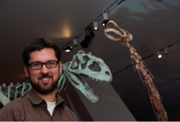David Evans standing in front of dinosaur skeletons