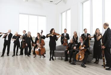 Tafelmusik Baroque Orchestra: musicians standing and playing in a white room